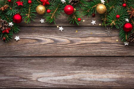 Photo pour Christmas and Happy New Year background. Fir tree branches and red with gold holiday decorations on rustic wooden table. top view. flat lay with copy space - image libre de droit
