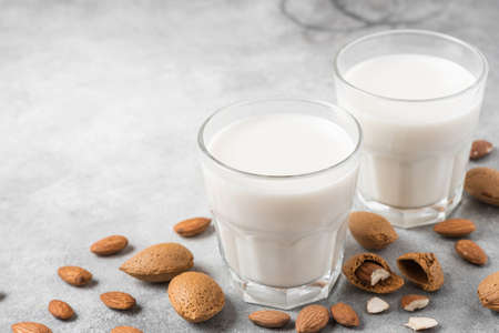 Photo for Plant based almond vegan milk in glasses with nuts on concrete background. Dairy free milk. close up - Royalty Free Image