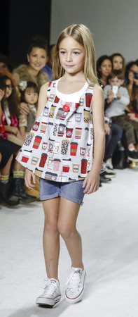 New York, NY, USA - October 19, 2014: A model walks the runway during the Aria Children's Clothing preview at petitePARADE / Kids Fashion Week at Bathhouse Studios, Manhattan