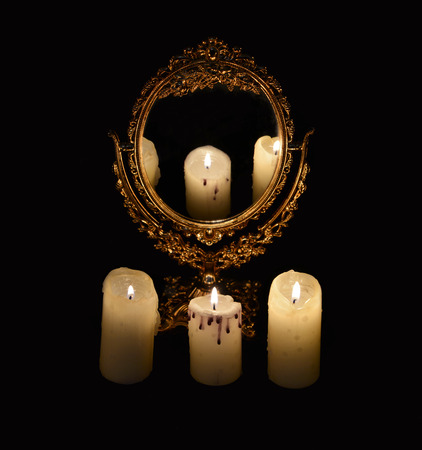 Mystic still life with mirror, reflection and three burning candles. Halloween concept, black magic ritual or spell with occult and esoteric symbols, divination rite. Vintage objects on witch table
