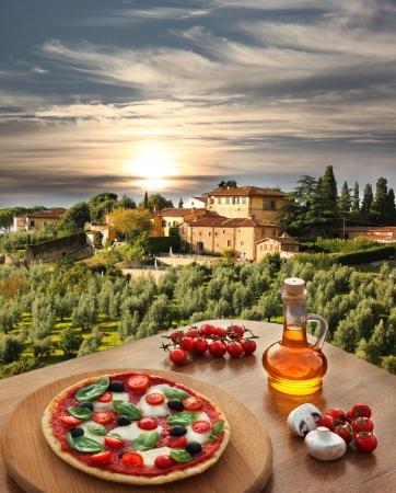 Italian pizza in Chianti against olive trees and villa in Tuscany, Italy