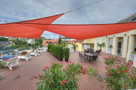 Terrace in summer with shade sails, flowers and deck chairs