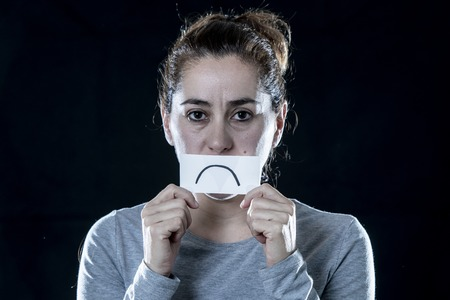 Young beautiful sad and depressed latin woman covering her sad face with a paper cut out sadder face in a depression concept on isolated black background.