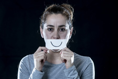 Young beautiful sad and depressed latin woman covering her sad face with a paper cut out happy face in a depression concept on isolated black background.