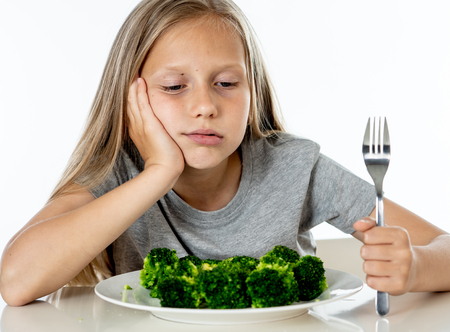 Photo pour Nutrition & healthy eating habits for kids healthy eating concept. Children do not like to eat vegetables. Little cute kid girl refuse to eat healthy broccoli vegetables on a white background - image libre de droit