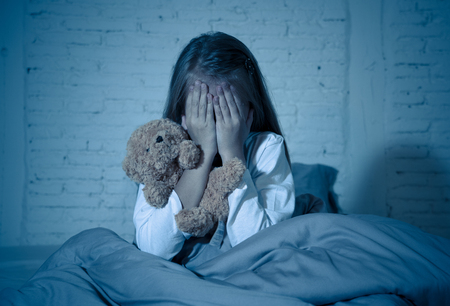 Photo pour Scared little girl sitting in bed covering her face with hands holding her teddy in fear afraid of monsters in darkness in bedroom in Child nightmares imagination and psychological distress concept. - image libre de droit