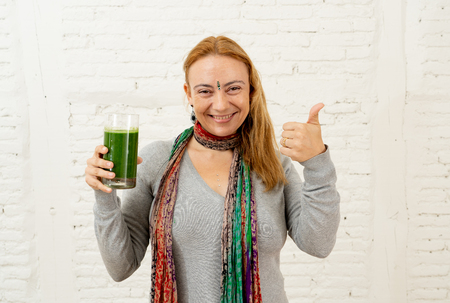 Cheerful woman smiling holding glass of green vegetable smoothie isolated on gray background in new lifestyle Fitness Ayurveda Diet Nutrition and Health beauty coach and Detox concept.