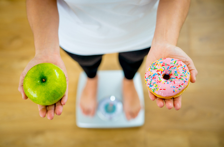 Close up of woman on scale holding on hands apple and doughnut ...