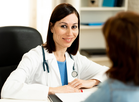 Smiling female doctor and happy patient talking and consulting in hospital clinic office in Health care, professional medical staff, happy hospital environment, Insurance and Medical trust concept.