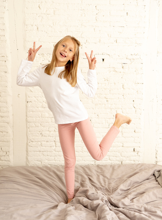 Photo pour beautiful cute blonde girl feeling happy and having fun jumping and playing on bed in her bedroom at home in kids happiness healthy lifestyle and family concept. - image libre de droit