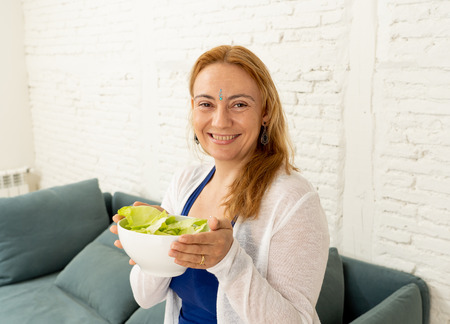 Cheerful woman showing bowl of green vegetable salad feeling happy of life change isolated on gray background in new lifestyle Ayurveda Diet Nutrition and Health beauty coach and Detox food concept.