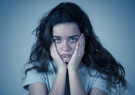 Portrait of beautiful sad miserable young teenager girl with unhappy face feeling emotional pain. Human facial expressions, negative emotions and childhood depression concept. moody background.