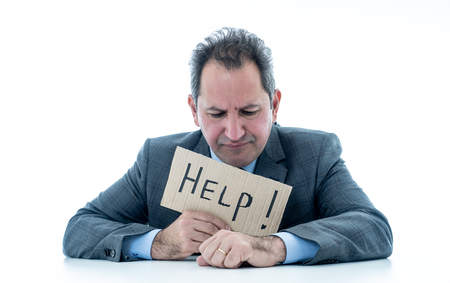 Foto de Depressed middle aged caucasian businessman desperate and tired holding a help sign looking frustrated, upset and unhappy. In business and stress at work frustration and unemployment concept. - Imagen libre de derechos