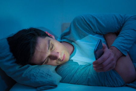 Photo pour Young mobile phone addict man awake at night in bed using smartphone for chatting, flirting and sending text message. In communication, Internet addiction and Social media network abuse concept - image libre de droit