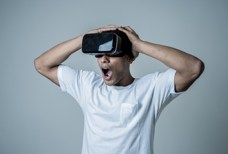 Photo pour Amazed african american man using VR headset glasses, feeling excited about simulation, exploring virtual reality making gestures interacting with new virtual world. In new technology concept. - image libre de droit