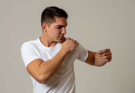 Photo pour Young muscular fitness man touching and grabbing his shoulder suffering strong pain. Isolated on neutral background. In sport injury Incorrect posture problems and body health care. - image libre de droit
