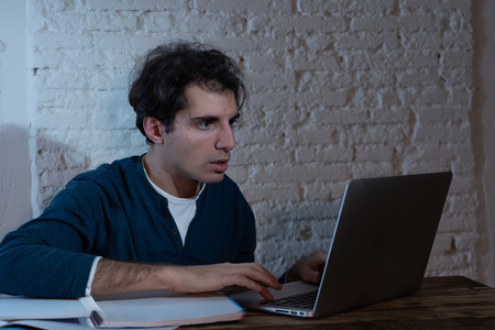 Photo pour Close up portrait in moody light of happy casual attractive man working and studying on laptop sitting on desk at night. In working from home, online learning and final exams concept. - image libre de droit