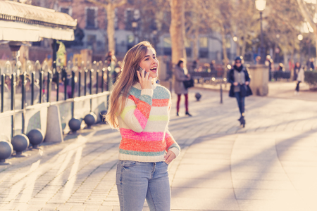Photo pour Pretty happy teenager woman talking on mobile smart phone outside city street. Beautiful stylish college student wearing fashion clothes feeling relaxed and free. Lifestyle, beauty and technology use. - image libre de droit