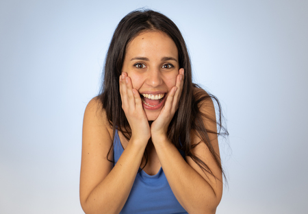 Excited latin teenager girl feeling amazed by Success Unbelievable sale Great news or Success screaming with joy. Funny woman euphoric winner. Portrait isolated on blue In People and human emotions.