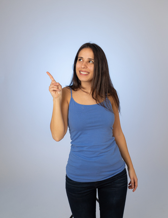 Photo for Beautiful latin young woman pointing finger at copy space looking cheerful happy and excited. Teenager girl showing something interesting isolated on empty background for text advertising content. - Royalty Free Image