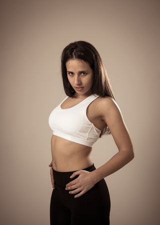 Photo pour Beauty portrait of sport confident young woman wearing gym top looking sensual and fit. Studio shot of cheerful latin strong woman in sportswear looking healthy and sexy. In fitness Body care concept. - image libre de droit