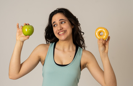 Photo for Beautiful young fit latin woman tempted having to make choice; apple and doughnut, healthy or unhealthy food. Fitness and nutrition healthy lifestyle and Diet concept. Studio shot with copy space. - Royalty Free Image