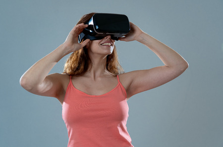 Foto de Amazed woman getting experience using VR headset glasses, feeling excited about simulation, exploring virtual reality making gestures interacting with new virtual world. In new technology concept. - Imagen libre de derechos
