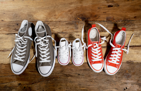 Photo pour Conceptual image of gumshoes sneakers shoes of father mother and son daughter family on vintage wood floor in different sizes in Sweet home togetherness Happy Family Parenting and lifestyle concept. - image libre de droit