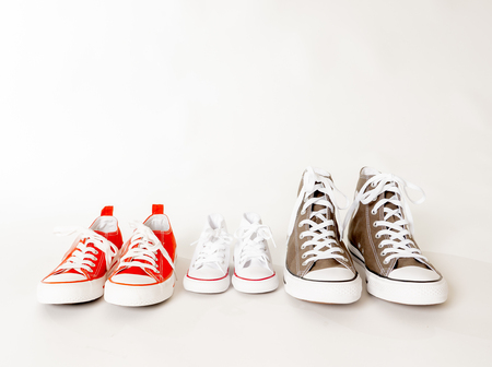 Photo pour Conceptual image of gumshoes sneakers of father mother and son daughter isolated on white background copy space in different sizes in togetherness Family Parenting Education and lifestyle concept. - image libre de droit