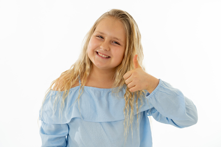 Photo pour Portrait of young schoolgirl feeling happy smiling and making thumbs up gesture. Isolated on neutral background. In Education Children, Human expressions and body language. - image libre de droit