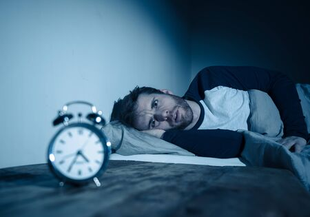 Photo pour Insomnia Stress and Sleeping disorder concept. Sleepless desperate young caucasian man awake at night not able to sleep, feeling frustrated and worried looking stressed and concerned at alarm clock. - image libre de droit