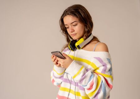 Photo pour Portrait of gorgeous and cheerful teen woman listening to music in headphones looking for online music on mobile on neutral background. In positive emotions, youth, people, leisure and technology concept. - image libre de droit