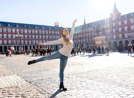 Photo pour Young attractive woman looking cheerful and excited posing and dancing in Plaza Mayor, Madrid, Spain. European city background. In tourism, student exchange in europe and holiday travel concept. - image libre de droit