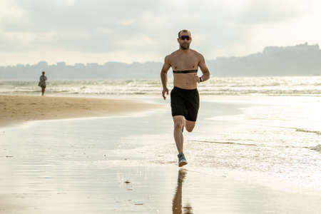Photo for Sports fitness man with heart rate monitor running on beach with smart watch. Fit body male runner doing jogging workout at the sea in sport exercise and technology and healthy lifestyle concept. - Royalty Free Image
