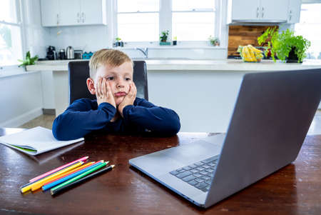 Photo for Coronavirus Outbreak. Lockdown and school closures. School boy with face mask watching online education classes feeling bored and depressed at home. COVID-19 pandemic forces children online learning. - Royalty Free Image