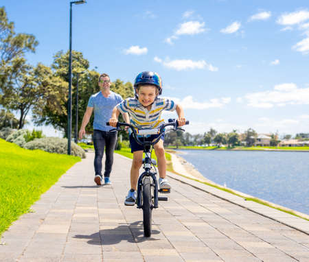 Photo for Boy learning to ride a bicycle with his father in the park by the lake. Father and son having fun together on the bikes. Happy family, outdoors activities, childhood and parenting concept. - Royalty Free Image