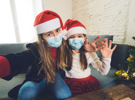 Photo for Sad and depressed children with mask at home bored at christmas feeling depressed missing family and friends. COVID-19 Lockdown, quarantine, stay home order, virtual christmas and mental health. - Royalty Free Image