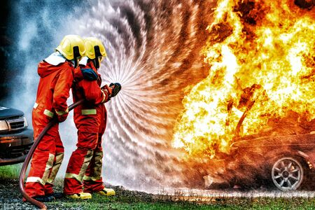 Photo for firefighter training., fireman using water and extinguisher to fighting with fire flame in accident car on the wayside road., under danger situation all firemen wearing fire fighter suit for safety. - Royalty Free Image