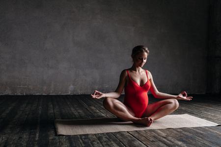 Young beautiful  pregnant yoga posing in studio