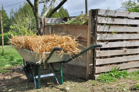 wooden composter for organic waste and wheelbarrow full of straw