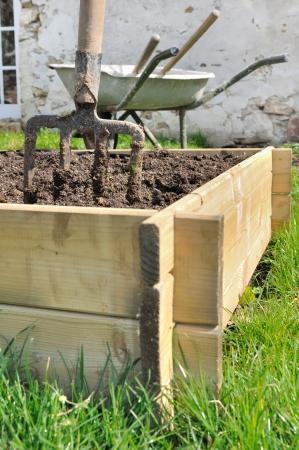 spade in a wooden  planter for vegetable garden
