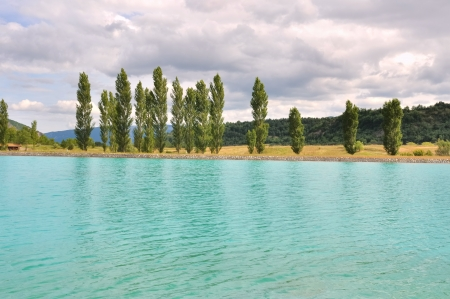 mountain lake with turquoise water under cloudy sky