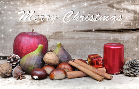 Seasonal fruits and cinnamon on christmas decoration with texte Merry Christmas