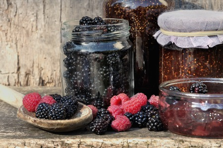 blackberry and raspberry with glass jars on wooden background