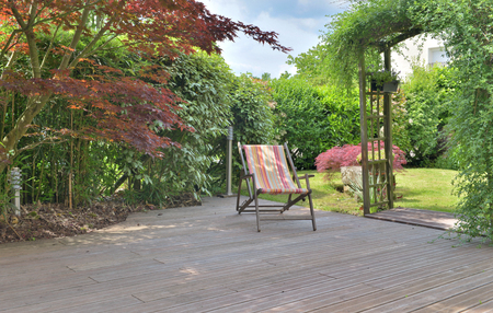 Foto per deck chair on a wooden terrace in a landscaped garden - Immagine Royalty Free