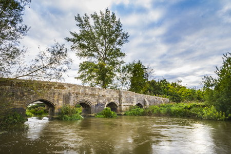 Photo for Old stone medival bridge over a streaming river in England. Dramatic cloudscape and old color tones - Royalty Free Image