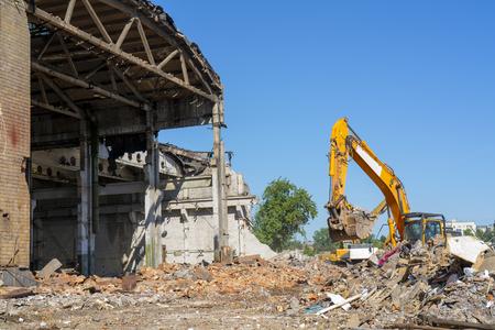 Photo pour Destruction of the old building. Yellow excavator on the ruins. - image libre de droit