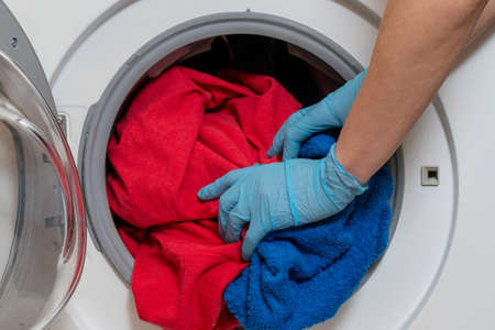 Photo pour Loading bed linen into a household washing machine. - image libre de droit