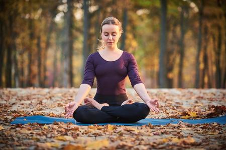 beautiful young woman meditates in yoga asana padmasana