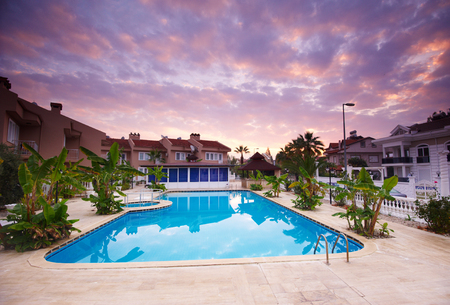 Swimming pool by the luxury resort hotel buildings at sunrise.